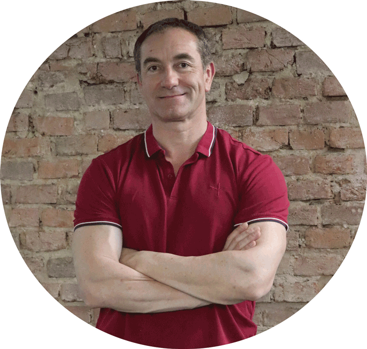 back pain coach standing arms crossed in front of red brick wall
