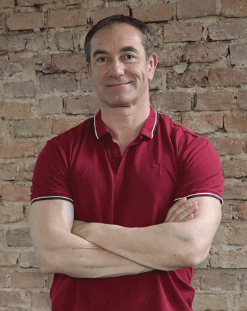 colin macgregor standing in front of red brick wall