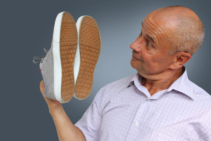 man looking at buying shoes to help with his lower back pain