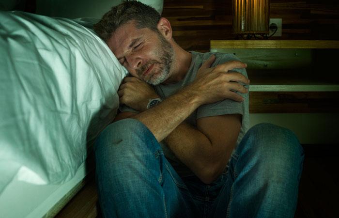 depressed man in pain sitting on floor beside bed