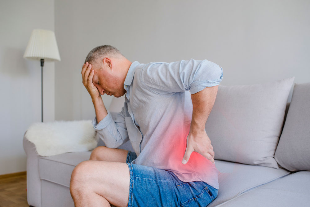 middle aged man holding head and lower back in pain on couch