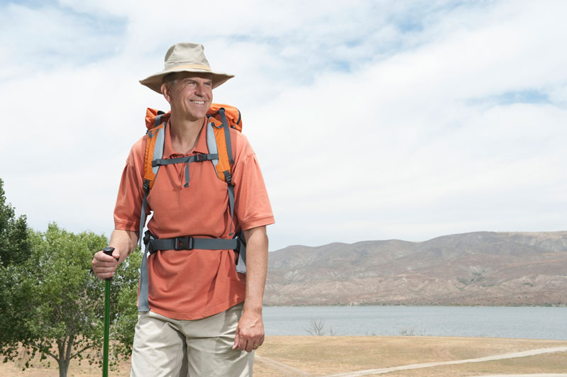 man hiking outside with lower back pain