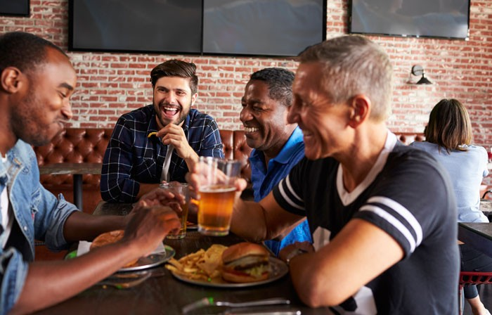 group of middle aged men eating and drinking and having a good time