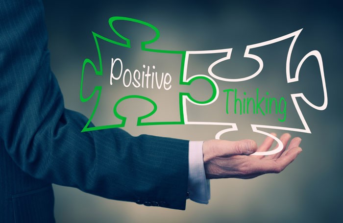 positive thinking text in jigsaw pieces on top of mans outstretched arm
