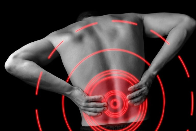 man with lower back pain holding his lower back