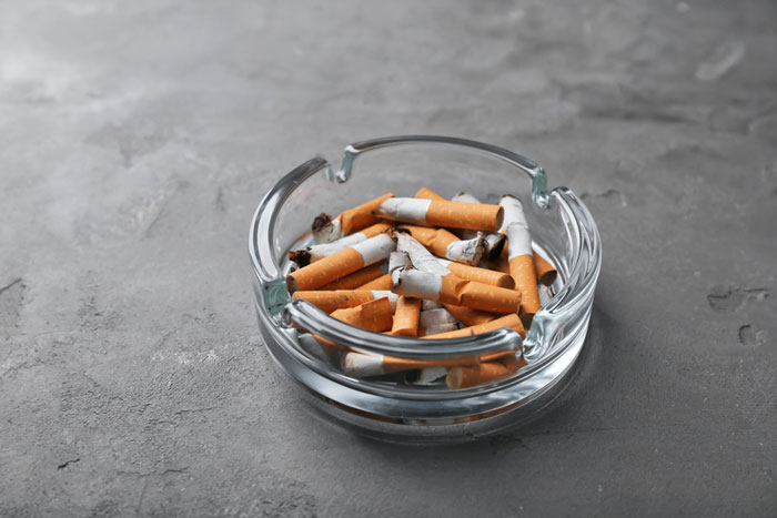 an ashtray filled with cigarettes and the influence of nicotine on lower back pain