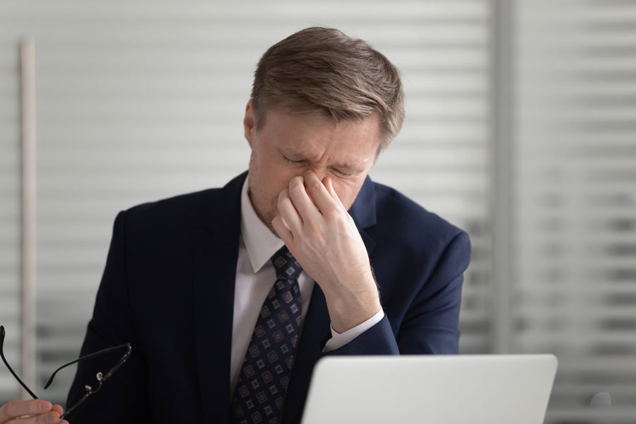 middle aged man with eye strain in front of laptop