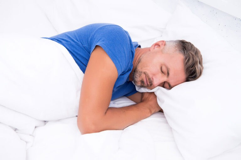 middle aged man sleeping on his side with lower back sciatica pain