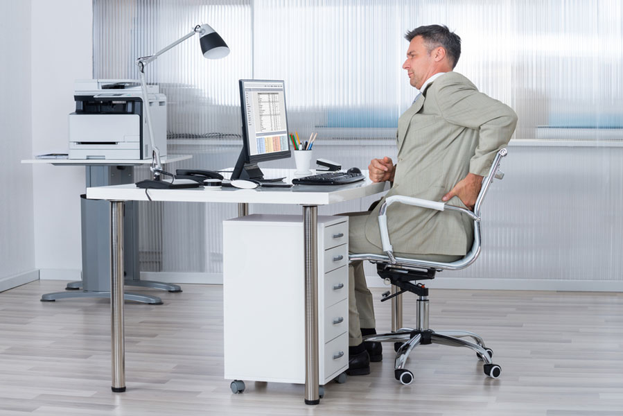 male office worker at desk with lower back pain