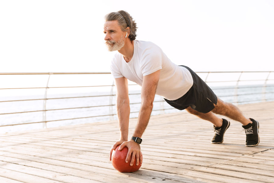 senior man on wooden deck performing front plank core exercise to prevent lower back pain
