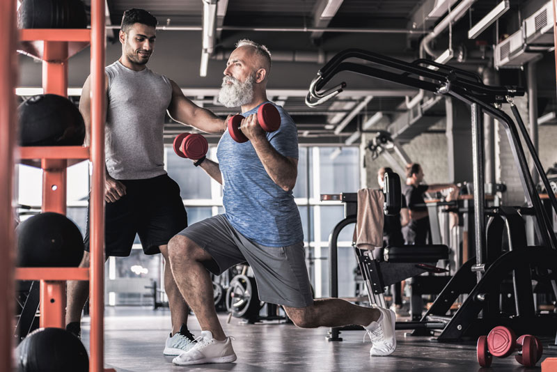 senior man with personal trainer doing exercise for lower back pain