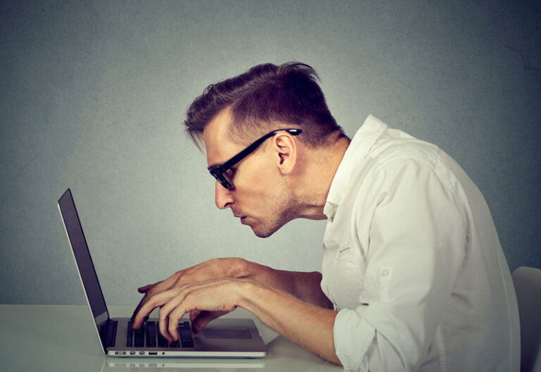 man hunched over laptop with back pain