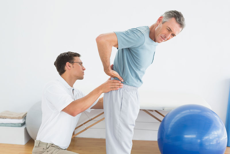 man receiving physiotherapy for lower back problem